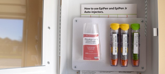 Open AEK cabinet shows inhaler and three epinephrine auto-injectors